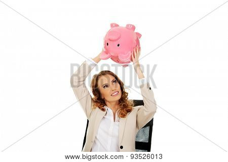 Business woman shaking a piggybank by a desk.