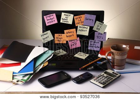 Laptop computer with messages on colorful papers, cellphone, smartphone, notebook, pen, pencil and e