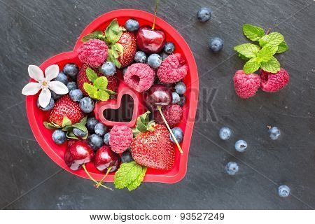 Mix Of Fresh Berries In A Red Silicon Backing Mold In Shape Of Heart , On Stone Gray Background, Top