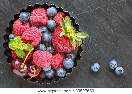 Mix Of Fresh Berries In A Small Round Metal Backing Mold, On Stone Gray Background, Top View, Horizo