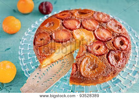 Homemade Upside-down Plum Cake On Glass Plate And Blue Background