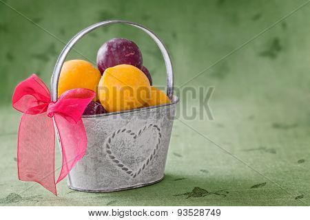 Old Tin Bucket With Red Ribbon Filled  Yellow And Red Plums On Green Background