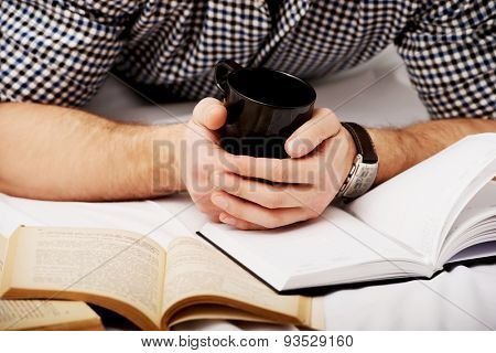 Thoughtful man with a book and coffee in his bed.