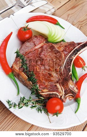 meat food : roast rib on white dish with thyme pepper and tomato on wooden table