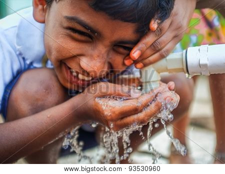 HAMPI, INDIA - 31 JANUARY 2015: Indian boy being teased while drinking water from a fauset