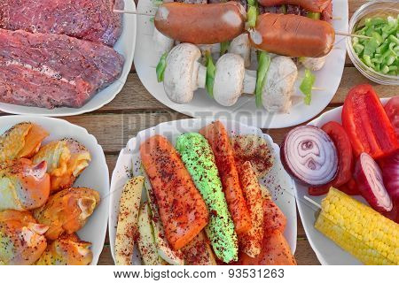 Table With Different Cookout Food On Plates For Bbq Party
