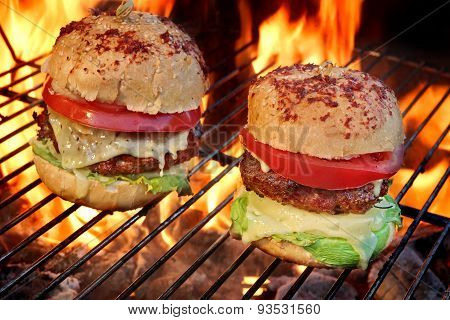 Two Homemade Cheeseburgers On The Flaming Bbq Grill