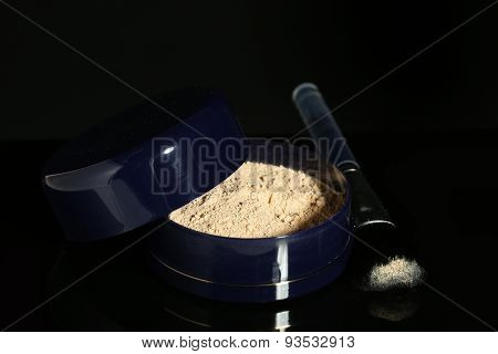 Jar with loose cosmetic powder and makeup brush, isolated on black