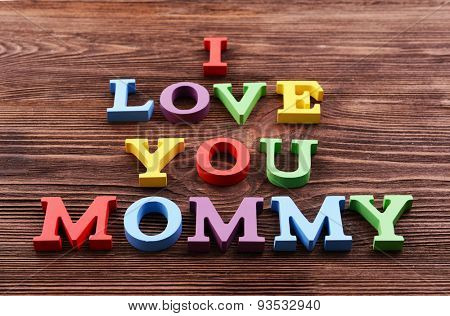 Inscription I LOVE YOU MUMMY made of colorful letters on wooden background