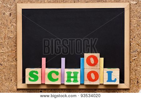 School word formed by wood alphabet blocks with small blackboard, isolated on white background