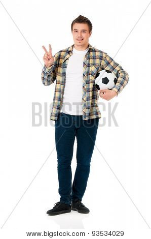 Young man standing with classic soccer ball showing victory sign isolated on white background