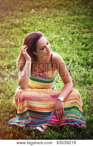 young woman in long colorful dress sit on grass enjoy in warm summer day on meadow