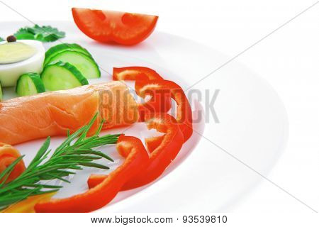 smoked salmon slices with vegetables over white plate