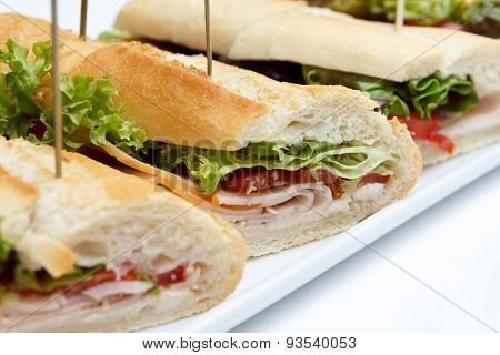 Platter Of Ham And Salad Baguettes On White.