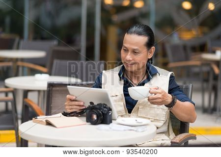 Man with coffee and digital tablet