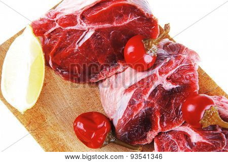 fresh raw beef meat medallion chunks on wooden plate isolated over white background with red hot peppers