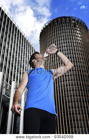 Young Sport Man Drinking Water Bottle After Running Training Session In Business District