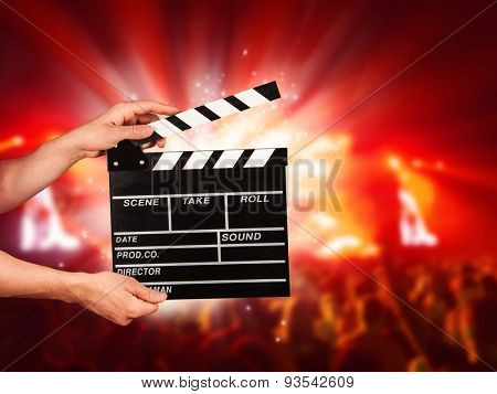 Man hands holding film clapper. Blur music concert on background