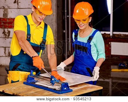 Happy group people of two person builder cutting ceramic tile.