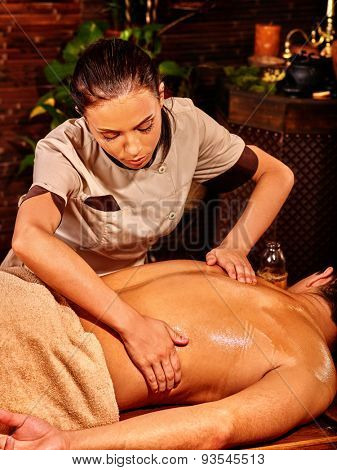 Man  having oil Ayurveda spa treatment. Visible male back.