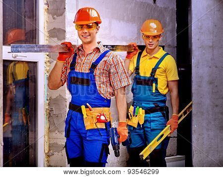 Happy strong men in builder uniform.