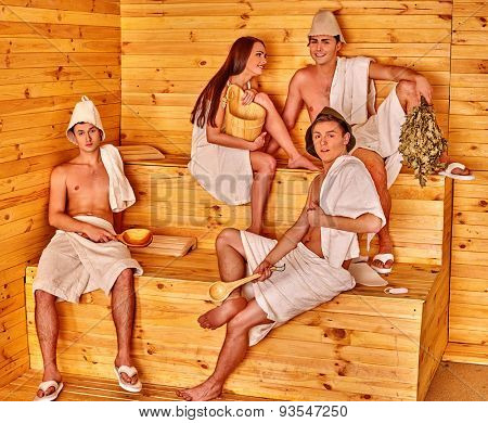 Group people and one girl  in hat  relaxing at sauna.