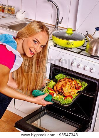 Young woman with long hair cooking chicken at kitchen.