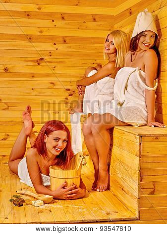 Happy three girlfriends relaxing in sauna.