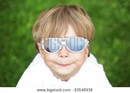 Happy cute kid in sunglasses against green natural background