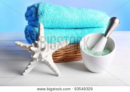 Rolled towels in wicker basket with starfish and sea salt on wooden table and light colorful background
