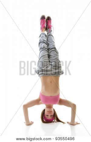 Teen girl hip-hop dancer standing on head over white background