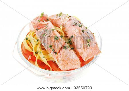 fresh fried natural pink salmon on italian traditional tagliatelles backed with tomato and vegetables isolated over white background