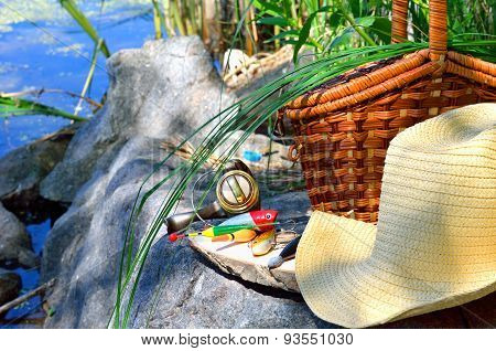 Fishing Tackle With Wicker Basket And Hat On The Lake Background