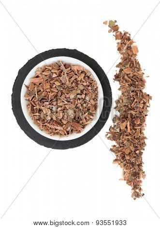 Witch hazel bark herb in a porcelain bowl and loose over slate round and white background.