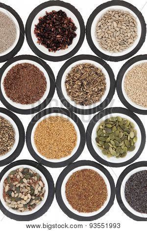 Seed food selection in porcelain bowls over slate rounds and white background.