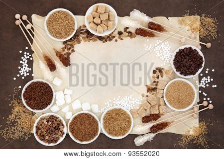 Brown and white sugar with crystal lollipops over parchment and  brown paper background.