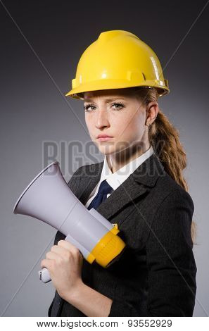 Female engineer with helmet and loudspeaker isolated on gray