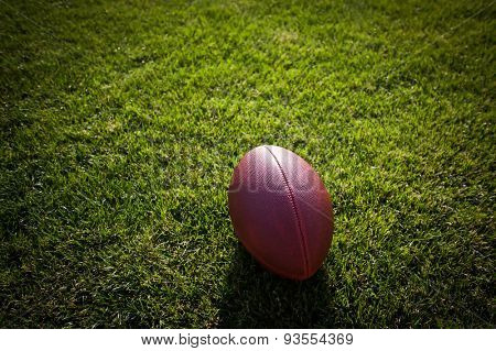 american football on stadium with out of focus players in the background