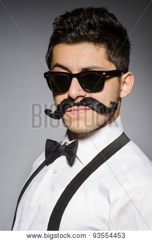 Young man with false moustache isolated on gray