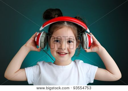 Beautiful little girl listening to music on color background