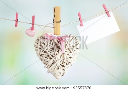 Hearts and card hanging on rope on bright background