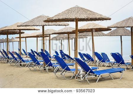 Rows of reed umbrellas and blue deck chair on the sea beach