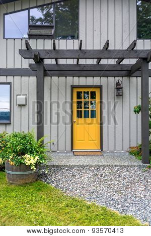Entrance of a luxury mid-century modern cottage house with yellow door