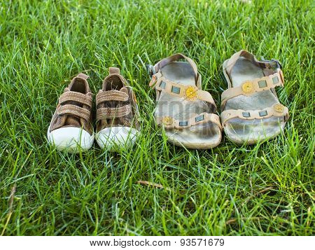 Baby Sneakers And Adult Slippers Are On The Grass.