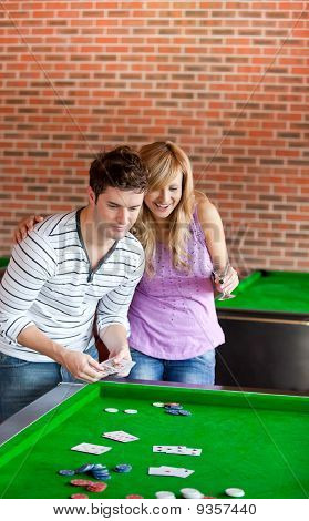 Cheerful Couple Playing Cards On A Billiard