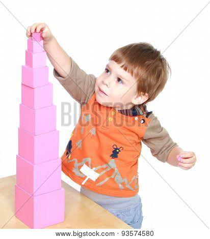 Little boy learn to put pink pyramid in Montessori kindergarten