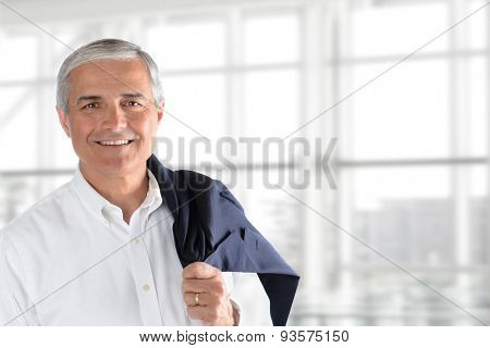 Closeup of a senior businessman holding his jacket over his shoulder in an office interior. Horizontal format with copy space.