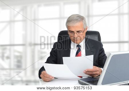 Closeup of a senior businessman looking at documents seated at his desk in modern office interior. Horizontal format with copy space.