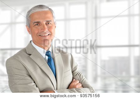 Closeup of a senior businessman with his arms folded in an office interior. Horizontal format with copy space.