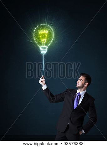 Businessman hold a shining idea bulb on a blue background